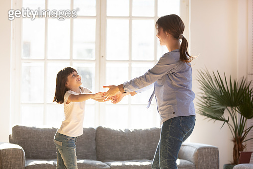 Happy mother having fun, dancing with adorable daughter at home