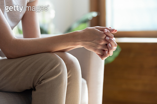 Closeup woman sitting on sofa with folded hands on knees.