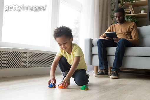 Family spend time at home kid play dad use tablet