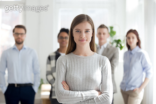 Female leader smiling looking at camera with team at background