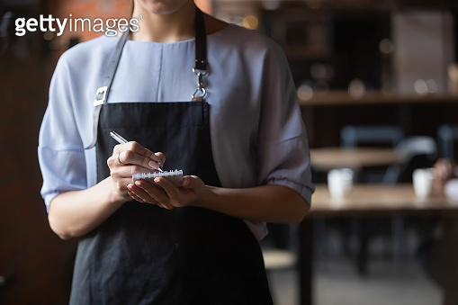 Close up attractive waitress ready to take order in coffeehouse