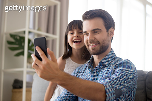 Smiling father taking selfie with cute kid daughter on smartphone