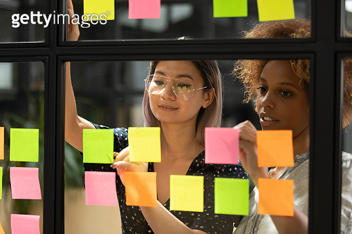 Businesswomen working together search solution of problem using sticky notes