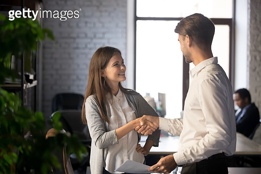 Male female colleagues greeting each other with handshake