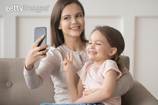 Cheerful funny mother holds smartphone take selfie with daughter