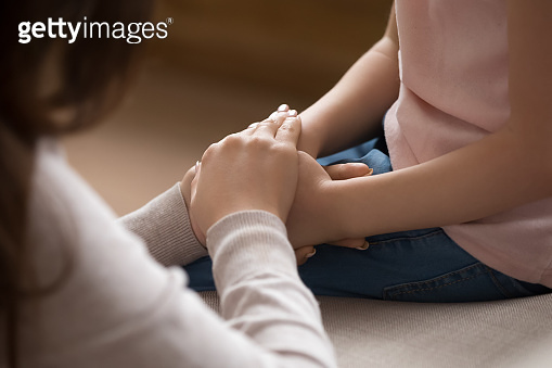 Close up of mother hands covers hands of little daughter