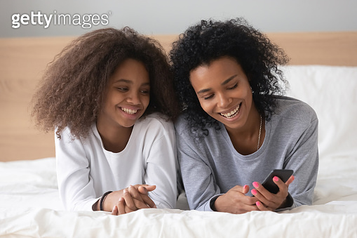 Smiling black mom and daughter relax with smartphone in bed