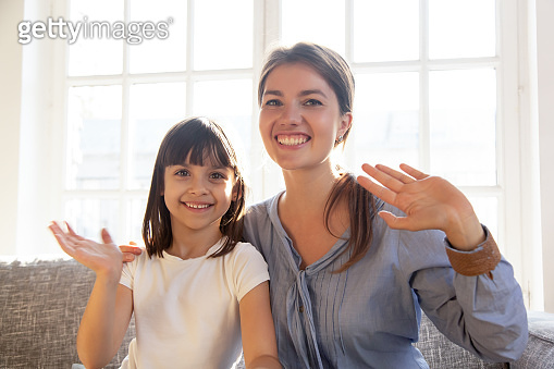 Happy mother and daughter looking at webcam and wave hands