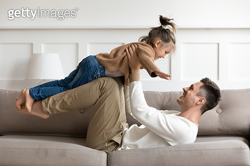 Happy father lifting cute kid daughter up playing on sofa