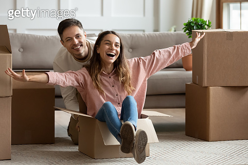 Happy  young couple riding in box on moving day