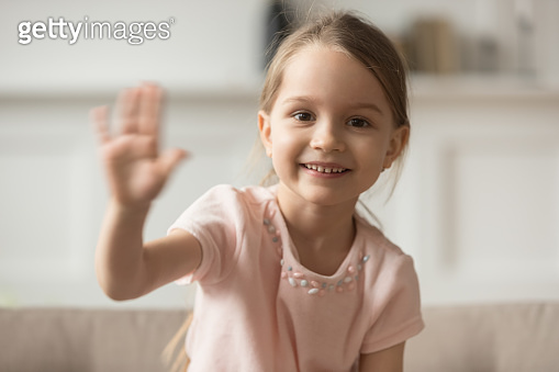 Little preschooler girl sit on couch waving looking at camera