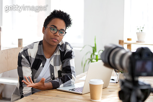 Serious african girl youtuber blogger talking to camera shooting video