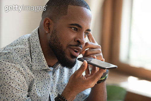 Close up thoughtful african american guy using virtual assistant.