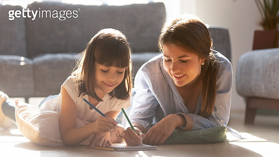 Mother drawing with daughter lying on warm floor