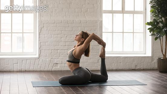 Woman practicing yoga, Rajakapotasana pose, One Legged King Pigeon