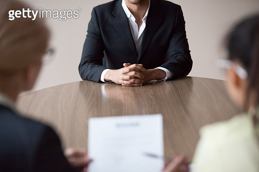 Job interview concept, african male job applicant talking to recruiters