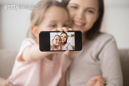 Smiling young mom and little daughter make cellphone selfie together