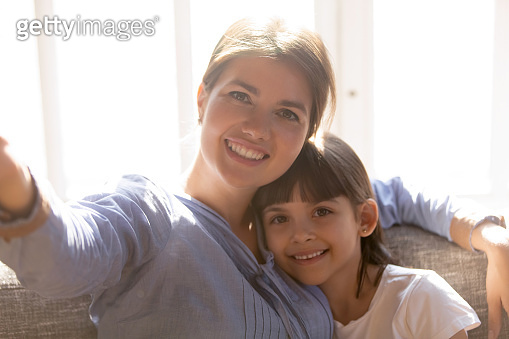 Smiling mom and little daughter make selfie together