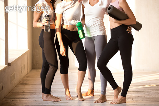 Legs of toned young girls standing after training