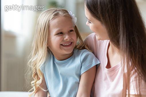 Happy adorable little preschool girl talking with positive mommy.