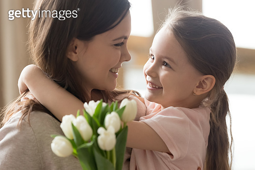 Happy kid daughter embracing mom receiving tulips on mothers day