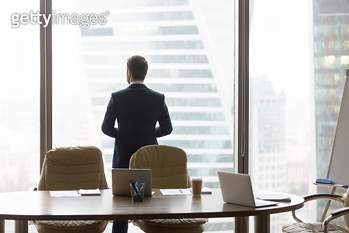 Rear view at successful businessman standing back in modern office