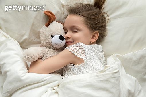 Cute little kid girl hugging teddy bear sleeping in bed