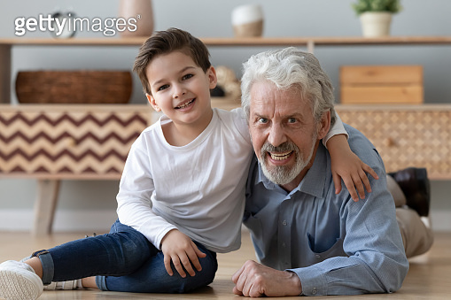 Portrait happy grandfather and little grandson sitting on warm floor