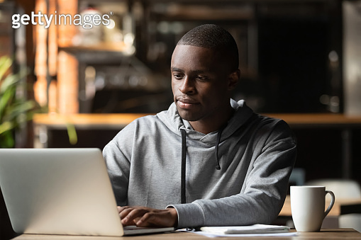 African American man using laptop in cafe, looking at screen