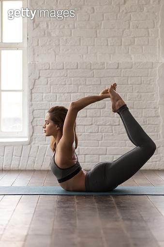 Woman practicing yoga, doing Dhanurasana exercise, Bow pose, vertical