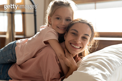 Little girl embracing mom lying on bed looking at camera
