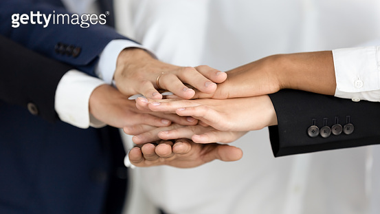 Diverse businesspeople group join hands in pile, close up view