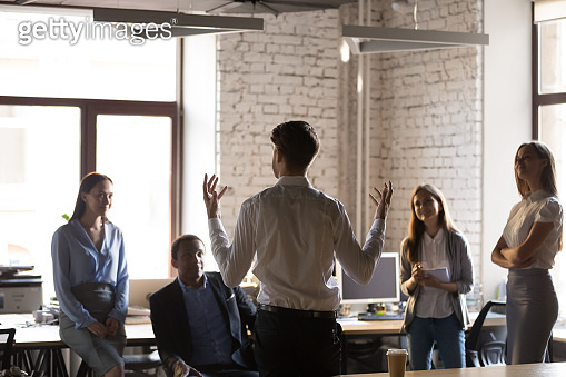 Diverse employees listening team leader during briefing