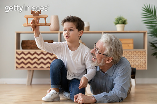 Happy grandfather and little grandson playing with wooden plane toy