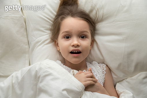 Above view frightened girl lying on bed looking at camera
