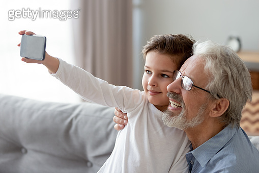 Happy grandfather and little grandchild taking selfie on phone