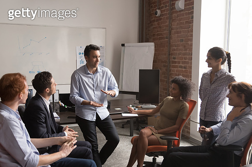 Diverse employees brainstorm sharing ideas at office meeting