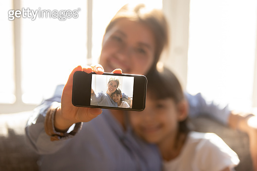 Happy mother embracing child daughter holding phone taking selfie