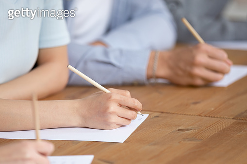 Close up of students writing passing test in classroom