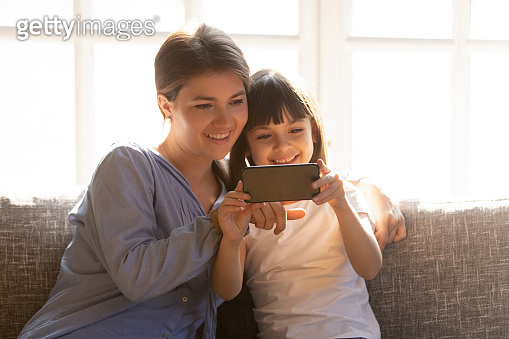 Happy mom and little child enjoy using smartphone at home