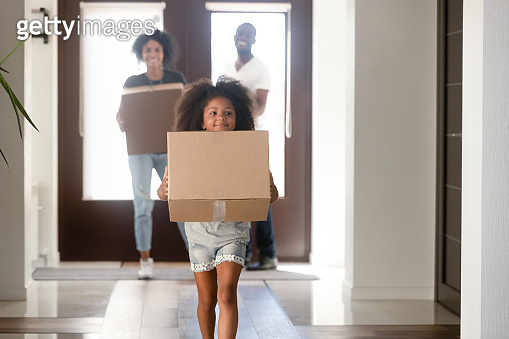Young family carry boxes moving to new home