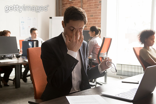 Exhausted male worker massage eyes suffering from headache
