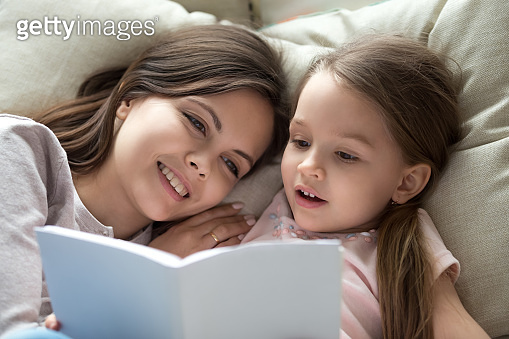 Happy mom listening child daughter learning reading book in bed
