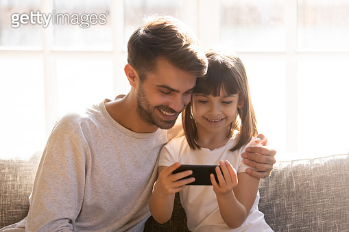 Happy dad and little child girl holding phone using smartphone