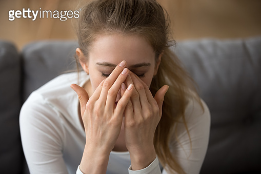 Close up thoughtful woman covered face in hands, feeling pain