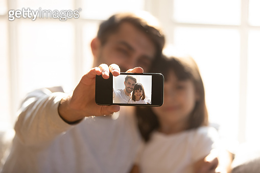 Father holding phone taking selfie with kid daughter on smartphone