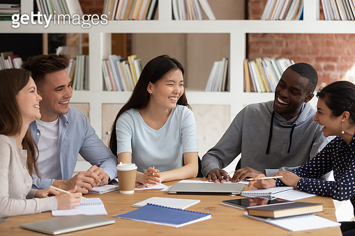 Happy mixed race college friends having fun during study break.