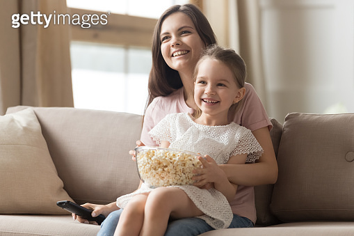 Happy mom and child girl laughing watching tv on sofa