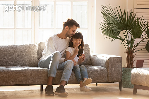 Happy dad embracing kid daughter enjoy using smartphone at home