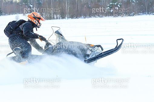 Man in a sports helmet rides a snowmobile